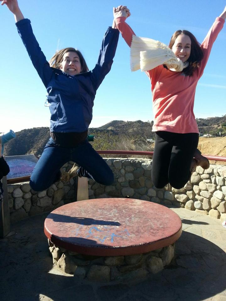 Claire and me holding hands while jumping off a low bench thing